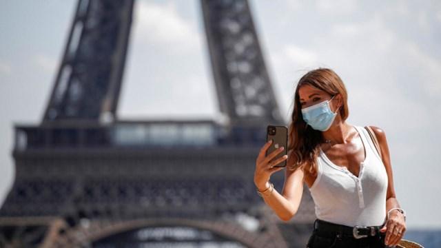 Một du khách đeo khẩu trang chụp ảnh tại tháp Eiffel. Ảnh: France 24.
