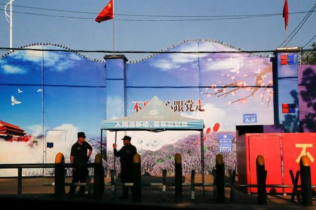 Nhân viên bảo vệ đứng gác ở cổng trung tâm dạy nghề ở khu tự trị Tân Cương, Trung Quốc - Ảnh: REUTERS