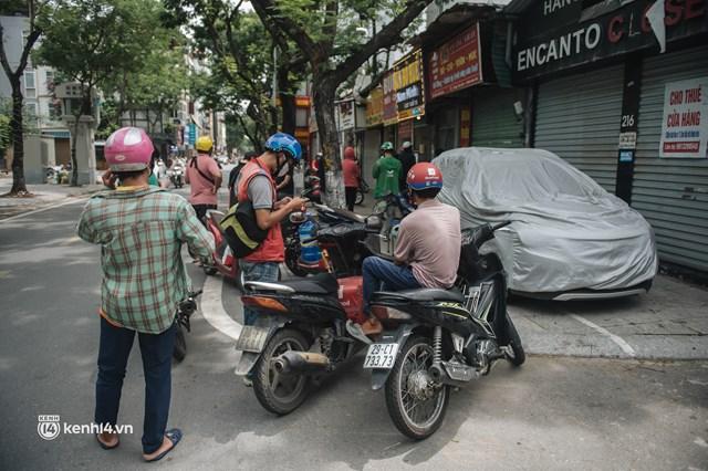 Hà Nội bắt đầu được giao đồ ăn trở lại: Shipper xếp hàng dài chờ mua trong khi khách gọi điện giục liên tục - Ảnh 10